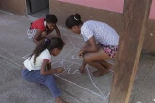Foto com três meninas ambas estão abaixadas, em circulo elas desenham em uma calçada com giz de lousa.