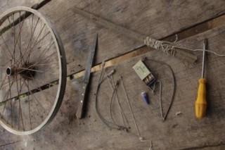 Foto com uma mesa de madeira, em cima várias ferramentas e peças.