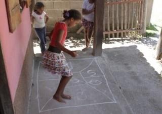 Foto com três crianças brincando, uma esta pulando amarelinha enquanto as outras duas observam.
