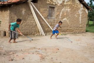 Foto com dois garotos brincando, com um eixo com duas rodas presas em suas extremidades, ele empurra com um graveto que está preso ao eixo.