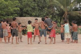 Foto composta por várias crianças em uma roda, de mãos dadas elas brincam.