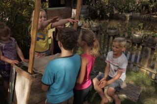 Foto de crianças brincando em volta de uma barraca.