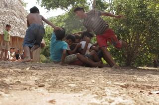 Foto de crianças sentadas em fila indiana, duas crianças correm em volta delas.