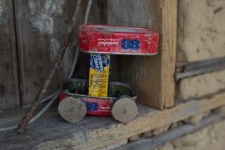 Foto de um carrinho feito de latas de sardinha.