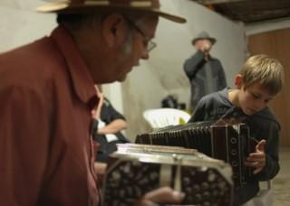 Foto de um senhor e um garoto, sentados eles tocam sanfona.