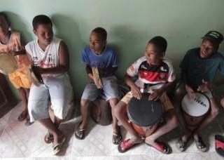 Foto onde cinco crianças estão tocando instrumentos, três estão tocando pandeiro e duas estão tocando tambor.