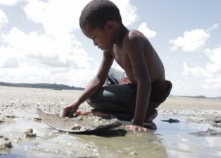 Foto com um garoto negro sem camisa ajoelhado, mexe em um chão lamacento.