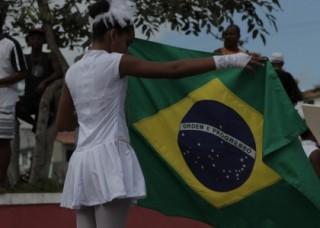 Foto de uma garota estendendo uma bandeira do Brasil.