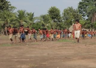 Foto com uma fila com crianças andam em fila indiana, algumas com as mão no ombro do próximo e outra com as mãos na cintura, um homem anda ao lado das crianças.