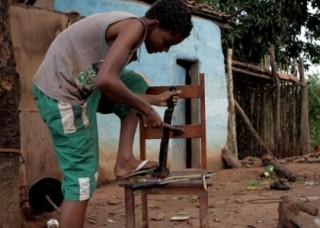 foto de um garoto negro que esta encurvado com seu pé esquerdo sobre a cadeira, com seu braço esquerdo apoia um facão em um pedaço de madeira em cima da cadeira, e com seu braço direito segura um martelo.