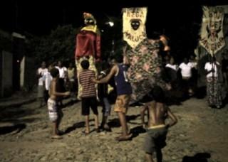 Foto ilustrando pessoas desfilando com bonecos grandes e bandeiras.