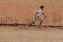 Foto de um garoto correndo ao lado de uma parede.