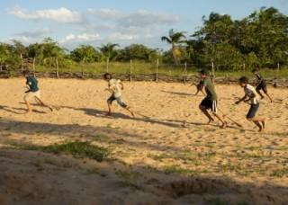 Foto composta por crianças correndo em um chão de areia, ambas as crianças estão com um galho de folha de um coqueiro entre as pernas, como se fossem cavalos.