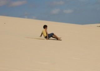 Foto com uma criança escorregando em uma montanha de areia.