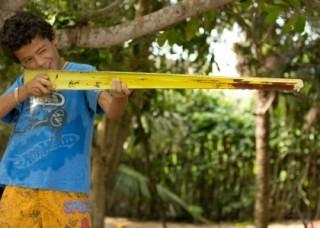 Foto de um garoto segurando uma folha de um coqueiro cortada só com seu meio, o garoto está segurando como se fosse um rifle, com um olho aberto e outro fechado ele mira.