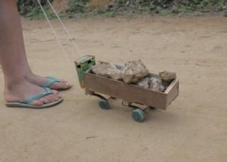 Foto ilustrando um caminhão de brinquedo feito de madeira carregando pedras, um garoto segura uma corda que está amarrado a este caminhão.