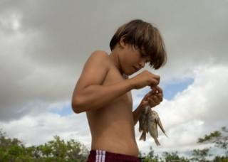 Foto de um garoto sem camisa, ele está segurando vário peixes em sua mão.