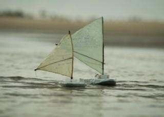 Foto com dois barcos a vela de brinquedos navegando sobre um lago.