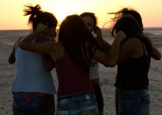 Foto ilustrando cinco garotas em círculo ao pôr do sol, cada uma delas estão com as mãos nas orelhas das pessoas ao seu lado uma mão, em cada pessoa.