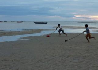 Foto demonstra dois garotos correndo na praia ao entardecer, cada um empurra seu brinquedo com um graveto que está amarrado a ele, o brinquedo é um eixo de madeira com carretéis em suas extremidades.