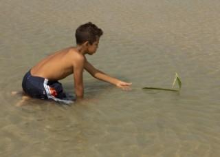 Foto de um garoto ajoelhado brincando dentro de um lago mexe em uma folha que esta boiando.