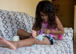Foto ilustra uma garota sentada em um sofá cortando um tecido que apoia sobre sua coxa esquerda, concentrada coloca a língua para fora.