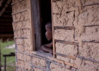 Foto com um garoto negro encostado em uma janela dentro da sua casa, observa fora.