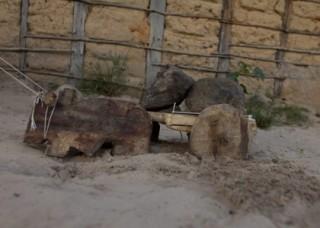 Foto de um brinquedo de um boi que puxa uma carroça feito de madeira, tem duas pedras em cima da carroça do boi, o brinquedo está sendo puxado com um barbante.