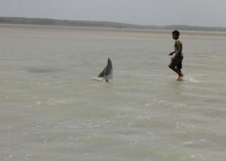Foto de um garoto dentro da agua em uma praia, brinca com seu barco a vela de brinquedo.