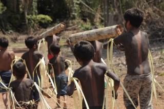 Foto composta por varias crianças andando com pinturas em seu corpo, algumas delas carregam troncos de madeira.