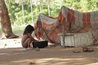 Foto de uma garota, abaixada ela mexe em uma bacia.