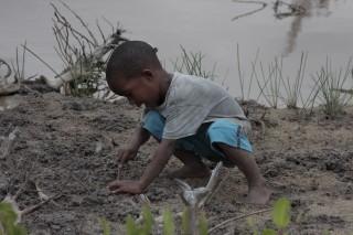 Foto de um garoto negro mexendo em um chão de terra.