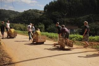 Foto ilustra várias crianças brincando com carrinhos de madeira, onde uma puxa o carrinho e outra fica em cima.