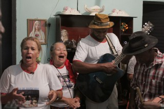 Foto de duas mulheres cantando e dois homens tocando instrumentos.