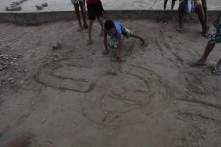 Foto de crianças brincando com uma tampinha em um chão de terra.