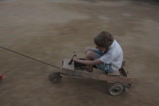 Foto com um garoto brincando em cima de um carrinho de madeira está sendo puxado por um cabo amarrado ao carrinho.