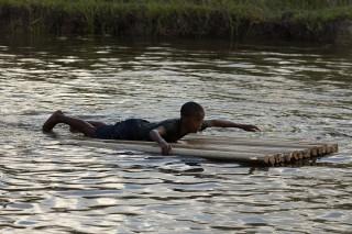 Foto de um garoto deitado de barriga em uma placa feita com galhos de galhos de folhas de bananeira, o garoto está remando com seus braços.