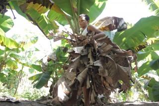Foto de um garoto vestindo uma saia feita de folhas de bananeiras ressecadas.