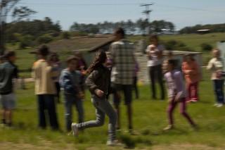 Foto com várias pessoas em uma roda, todas estão borradas, uma garota que tem o foco está correndo em volta destas pessoas.