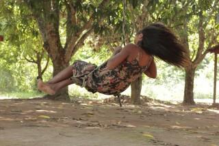 Foto de uma garota balançando de baixo de uma arvore ao entardecer do dia.