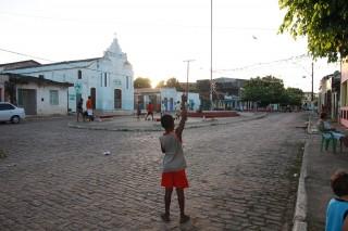Foto de um garoto em uma praça empinando uma pipa.
