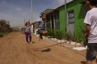 Foto demonstra três crianças brincando de pular corda, um garoto esta saltando, enquanto outras duas crianças, um menino e uma menina, estão batendo a corda.