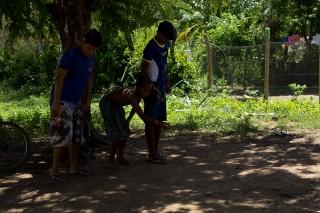 Foto com três garotos brincando de bolinha de gude em baixo de uma arvore.
