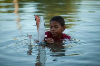 Foto de um garoto dentro de um lago, brinca com um barco a vela de brinquedo.