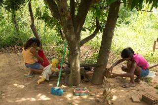 Foto com duas meninas brincando de casinha ambas abaixadas uma mexe em um saco vermelho enquanto outra mexe em uma mesa de brinquedo feito de madeira com alguns utensílios, vários brinquedos estão espalhados.