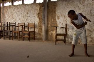 Foto com um garoto brincando de peão, onde logo após ter arremessado um peão, o garoto puxa a corda.