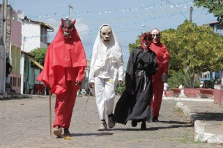 Foto com quatro pessoas fantasiadas, ambas vestem máscaras assustadoras.