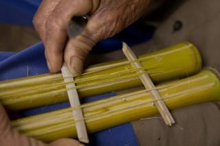Foto ilustrando um instrumento de brinquedo no colo de um homem, o brinquedo é feito de bambu.