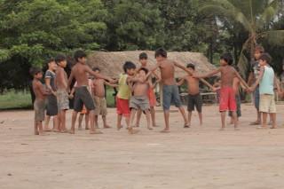Foto composta por várias crianças de mão dadas brincam e m uma roda.