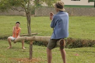 Foto de dois garotos brincando em uma gangorra feita com um tronco de madeira, um garoto tem um boné azul e outro usa um chapéu marrom.